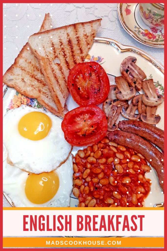 English breakfast with baked beans, sausages, tomatoes, mushrooms, and sunny-side-up eggs.